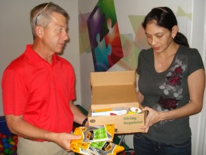 Larry presents a small gift of school supplies from Friends of Cozumel to Carla during their tour.