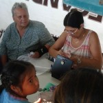 Ilene (left) and April (right) help people count the pesos needed for their purchases.