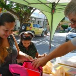 FOC volunteer Gary (right) helps Monse (left) fill her backpack with the supplies required for her university classes.