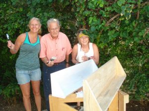 (from left) Kristin, Ray and Lori paint shelves as part of the construction project.