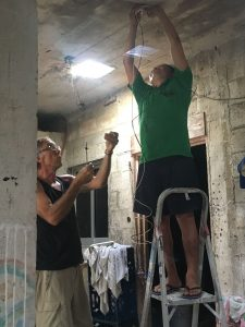 John (left) and Victor work together to install a light.