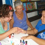 Amy (left) and Janet (center) help with manicures at a family fun night.