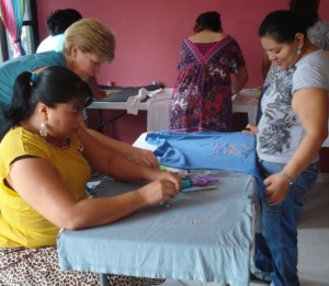 Mariela lays out a t-shirt to make into a diaper as Karen and Elena watch.