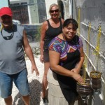 Pastor Mariela (right) plants seeds after Gary (left) and Kristin (center) created containers in the new hanging garden