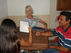 Volunteers Rita (center) and Pastor Salomon (right) helped fit reading glasses.