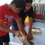 2 boys share tools and advice on the mirror project.