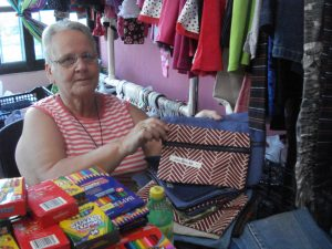 Ilene shows one of the many pencil bags she and other volunteers made.