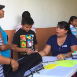 Pastora Mariela (right) helped identify families in need and check them in..