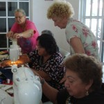 Chris (upper right) and Ilene (left) help seniors learn to sew.