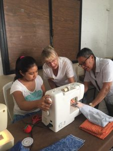 Perla gets sewing advice from FOC volunteers Marion and Tania.
