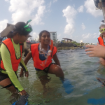 Volunteer Sami (left) helps a new snorkeler put on her fins.