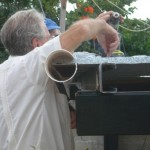 Ray uses PVC pipe and shelf braces to fashion a roof gutter.