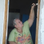 Ilene applies finish to a window frame to protect it from the weather.