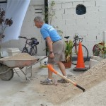 Larry works on moving a mountain of sand for the concrete work.